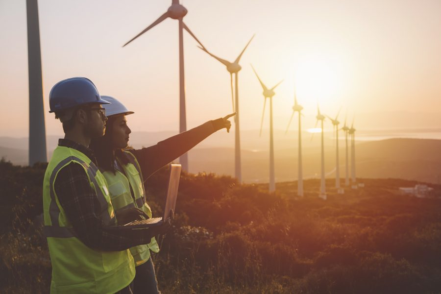 construction workers pointing with wind turbines in the background