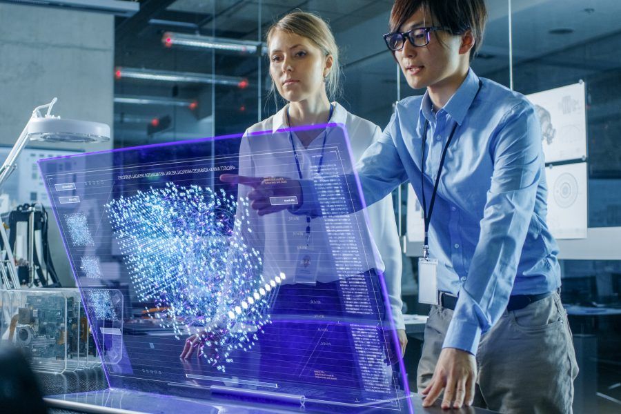 Male and Female Engineers Have Discussion while Using Modern Computer With Transparent Holographic Display. Monitor Shows User Neural Network Architecture Visualization. Shot in Modern Glass and Concrete Office.