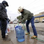 Leovardo Perez, right, fills a water jug using a hose from a public park water spigot Thursday, Feb. 18, 2021, in Houston. Houston and several surrounding cities are under a boil water notice as many residents are still without running water in their homes.David J. Phillip/AP Photo